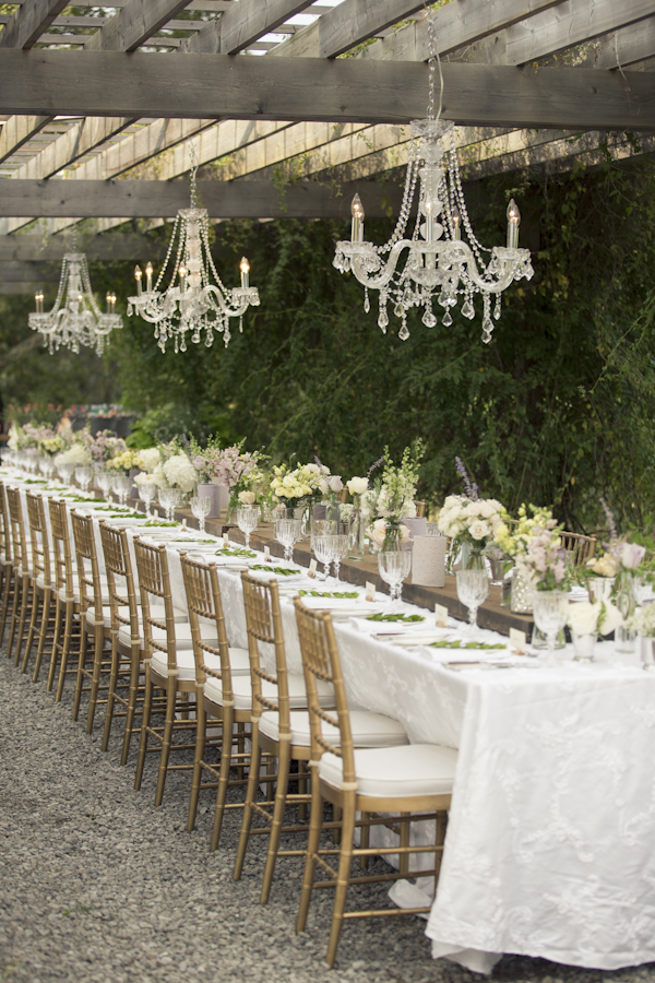 Chandeliers handing over communal table at outdoor wedding reception communal table at Niagara winery Good Earth