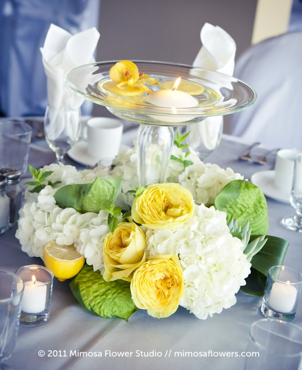 Wedding centerpiece featuring floating candle, yellow roses and glass