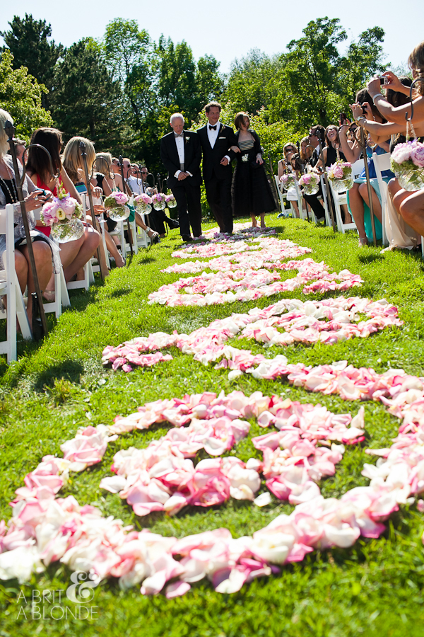 Outdoor wedding ceremony on farm walking down rose petal covered aisle
