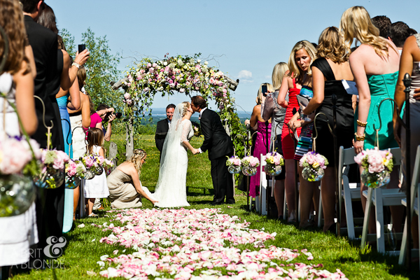 Outdoor wedding ceremony on farm walking down rose petal covered aisle bride and groom kissing