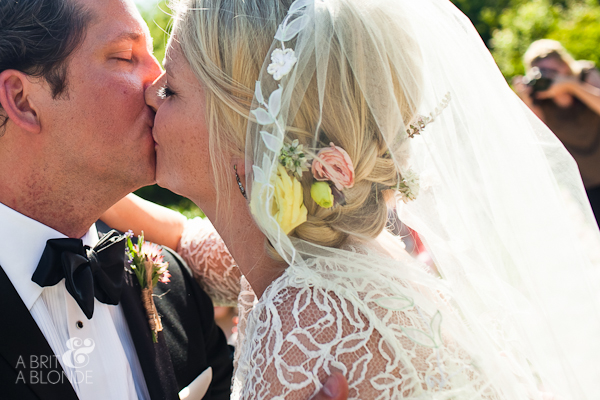closeup of bride and groom kissing on horse farm