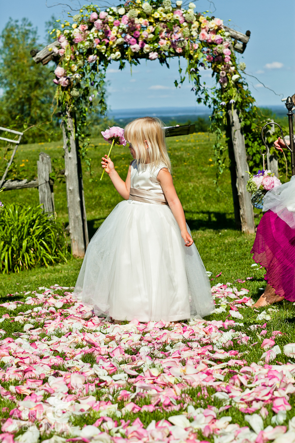Outdoor wedding ceremony rose petal covered aisle with flower girl