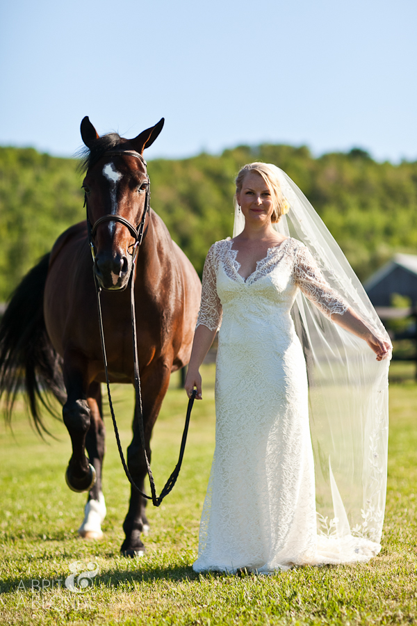Bride in lace gown standing with horse