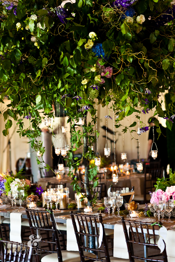 Outdoor wedding reception with giant tree covered in branches and salal