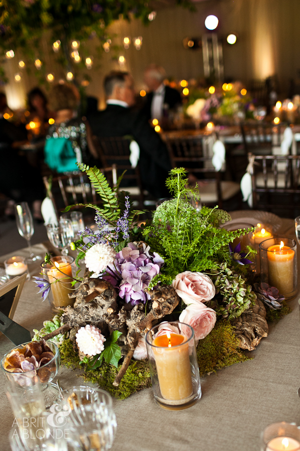 closeup of cork wedding reception centerpiece with ferns and flowers