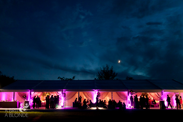 wedding reception outside tent at night with glow of candlelights