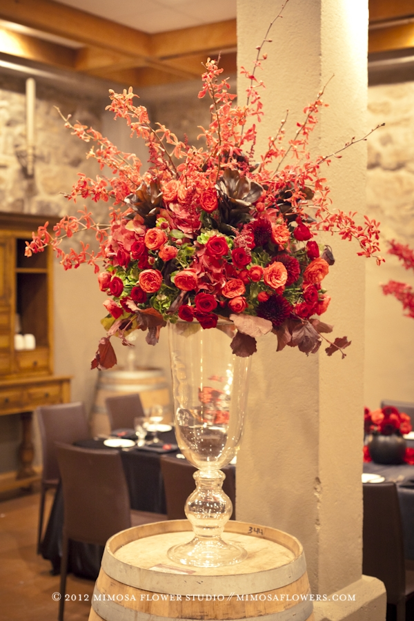 Large floral arrangement on a wine barrel with red orchids at Inn on the Twenty