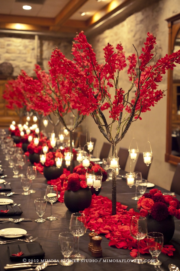 A table full of red orchids on a twiggy metal tree in the Vintner's Cellar at Inn on the Twenty