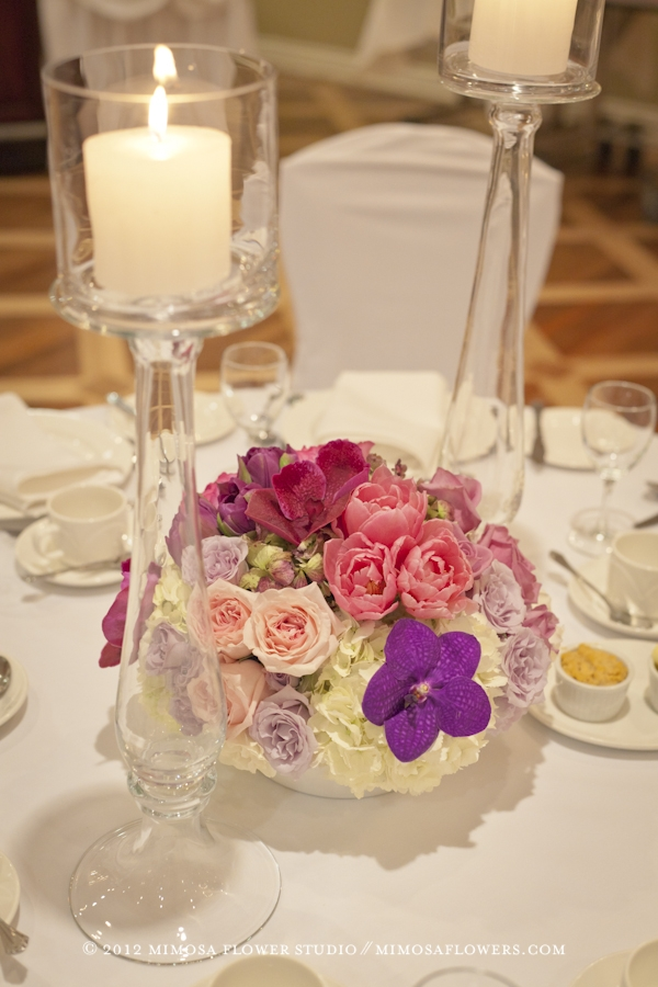 Full floral centerpiece with twin glass candlesticks at reception