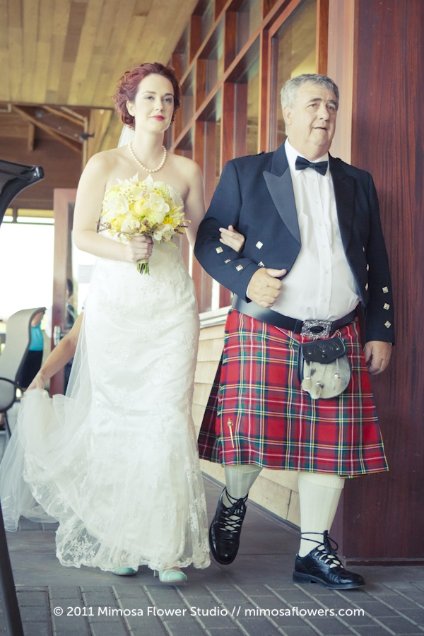Bride and Father walk down aisle with yellow bride's bouquet